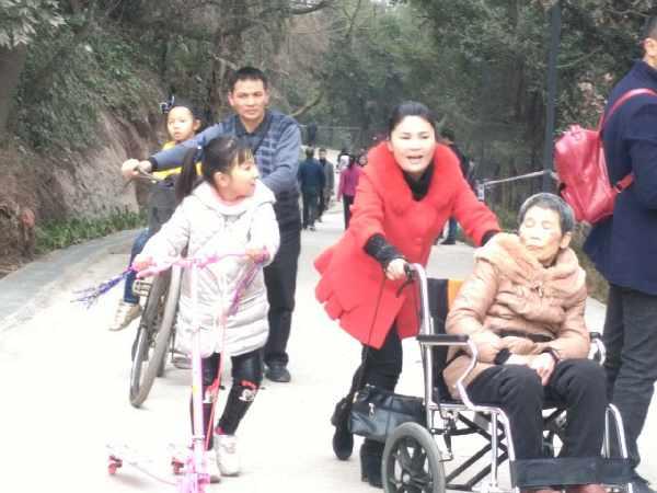 推着坐轮椅的妈妈登高